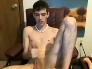 Scrawny twink is sitting on computer chair and hotly jerking off his dick